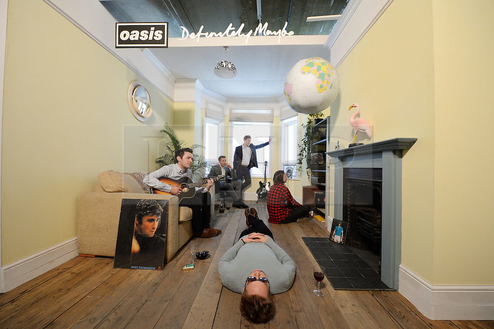 """© Licensed to London News Pictures. 15/04/2014. CITY/TOWN e.g Windsor, UK. Oasis fans recreate the album cover """"Definitely Maybe"""" at the Chasing the Sun exhibition, LondonNewcastle Project Space, London. The show, Oasis: Chasing The Sun, celebrates the four years in which the Burnage band went from unsigned act to stadium superstars, and includes original instruments, tour memorabilia, Noel Gallagher's handwritten lyric sheets and pictures from the photoshoots that got their faces on the covers of international magazines.. Photo credit : Mike King/LNP"""