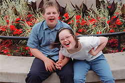Teenage boy and girl with Downs Syndrome sitting together in park holding hands and laughing,