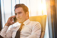 Mature businessman talking on smartphone with yellow lens flare