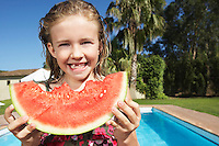 Portrait of girl (5-6) eating watermelon by swimming pool