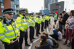 London, UK. 7 September, 2019. Metropolitan Police officers form a cordon in front of activists taking part in a sixth day of Stop The Arms Fair protests outside ExCel London against DSEI, the world's largest arms fair. The sixth day of protests was billed as a Festival of Resistance and included performances, entertainment for children and workshops as well as activities intended to disrupt deliveries to ExCel London for the arms fair.