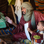 Mohammed Ould Mine with his son at the Mbera refugee camp in southeastern Mauritania on 1 March 2013. Originally from the region of Timbuktu in Mali, Ould Mine says this is his second sojourn at Mbera - he was resident here from 1992 to 1996 after the 1991 instability in Mali. He says he and his family will not return unless there is a clear, long-term outlook for political stability.
