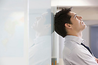 Unhappy Businessman leaning back against office wall and looking at ceiling side view