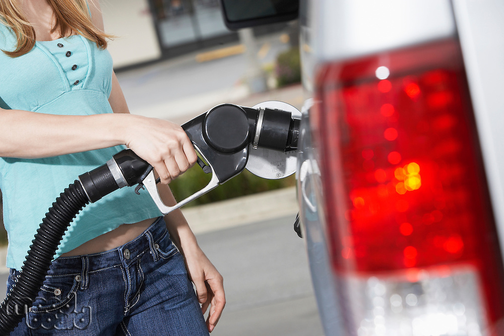 Young woman filling car with gas at gas station mid section