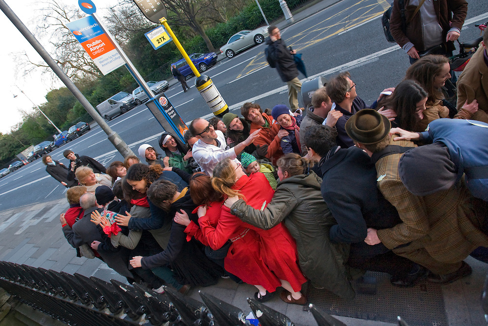 Audience performs a lap sit during Professor Coyle's Physics Experiments, Merrion Square Dublin, outside Dublin Institute of Advanced Studies, School of Cosmic Physics, on the Walking Tour of Places of No Historical Interest , Festival of Fools, April 1st 2009, marking April Fool's Day, and the 43rd anniversary of the death of Irish author Flann O'Brien