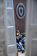 A student at the Stark Campus reads a book on a warm spring day. The student is sitting in a plaza near the main hall.
