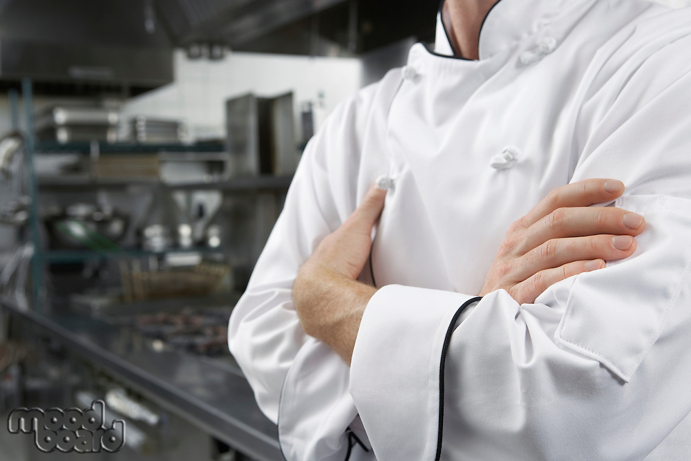 Male chef with arms crossed in kitchen mid section