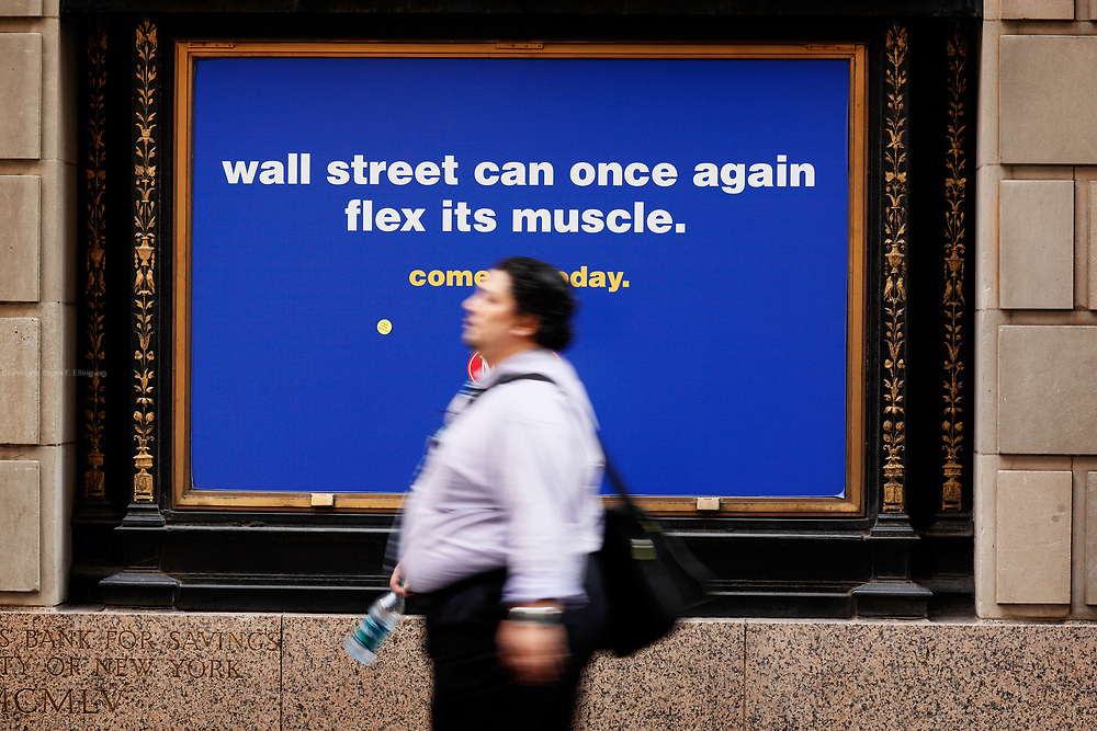 """An ad on Wall Street for New York Sports Club states """" Wall Street can once again flex it's muscles. """" Stocks on Wall Street surge in the morning, reacting to the 117k jobs added in the last week."""