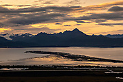 Storm clouds part at sunset over Grewingk Glacier and the Homer Spit along the Kachemak Bay State Park from Homer, Alaska.