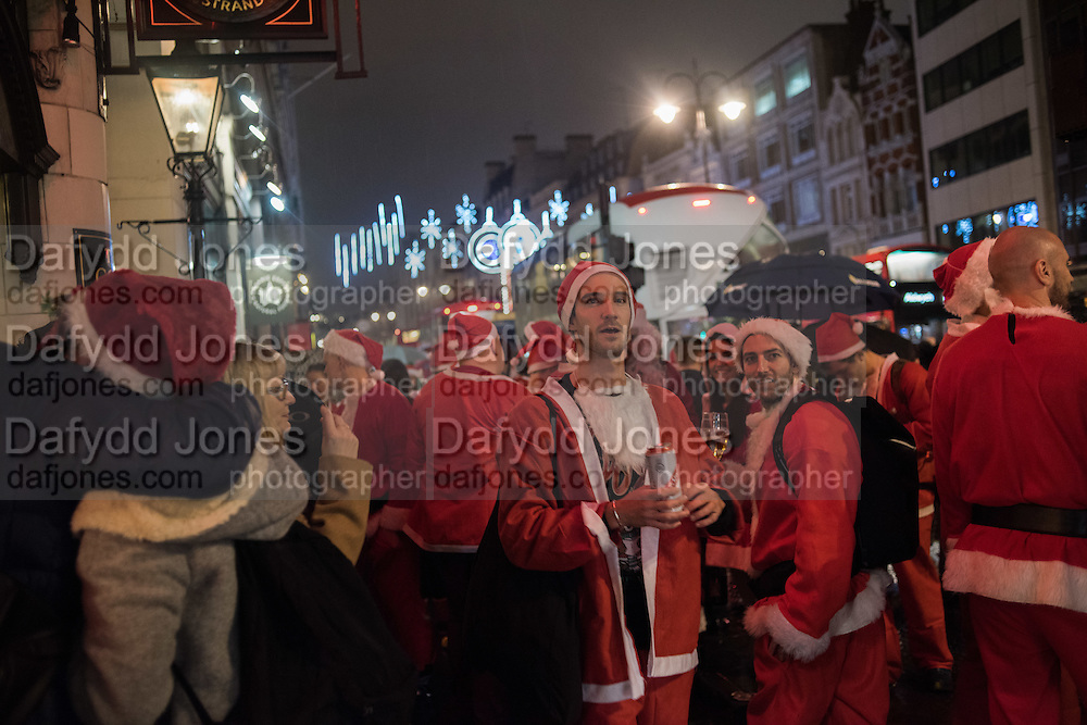 Revellers dressed as Father Christmas on a pub crawl, Strand, , London. 10 December 2016