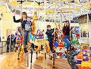 Garden City, New York, USA. March 9, 2019. People, including, at extreme left, a mother with her young son, and, at extreme right, Cayla Kempf, are riding carousel horses during Unveiling Ceremony of Nunley's Carousel mural. The Kempf family, according to Colette Kempf, is related to Bassett, who was a silent partner of the carousel's original owners, the Murphy Brothers of Murphy's Carousel Company.  Event was held at historic Nunley's Carousel in its Pavilion on Museum Row on Long Island.