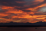A Washington state ferry crosses the Puget Sound from Seattle to Bremerton as a fiery sunset lights up the sky above the Olympic Mountains.