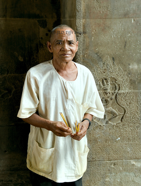 Incense seller outside a Buddhist shrine in the Angkor Wat temple precinct.  The wall behind him has a small sculptured relief of Apsara dancers.  H is middle aged, rather good looking, and his face seems timid and anxious with a core of strength and determination underneath.