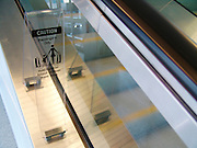 Plastic warning sign to take caution when riding the escalator with a child next to an escalator.