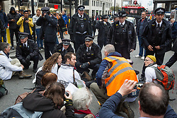 London, UK. 14 October, 2019. Police officers serve notices under Section 14 of the Public Order Act 1986 to climate activists from Scientists for Extinction Rebellion who had blocked the busy junction at King William Street in front of London Bridge on the eighth day of International Rebellion protests across London. Today's activities were concentrated around the  City of London's finance district.