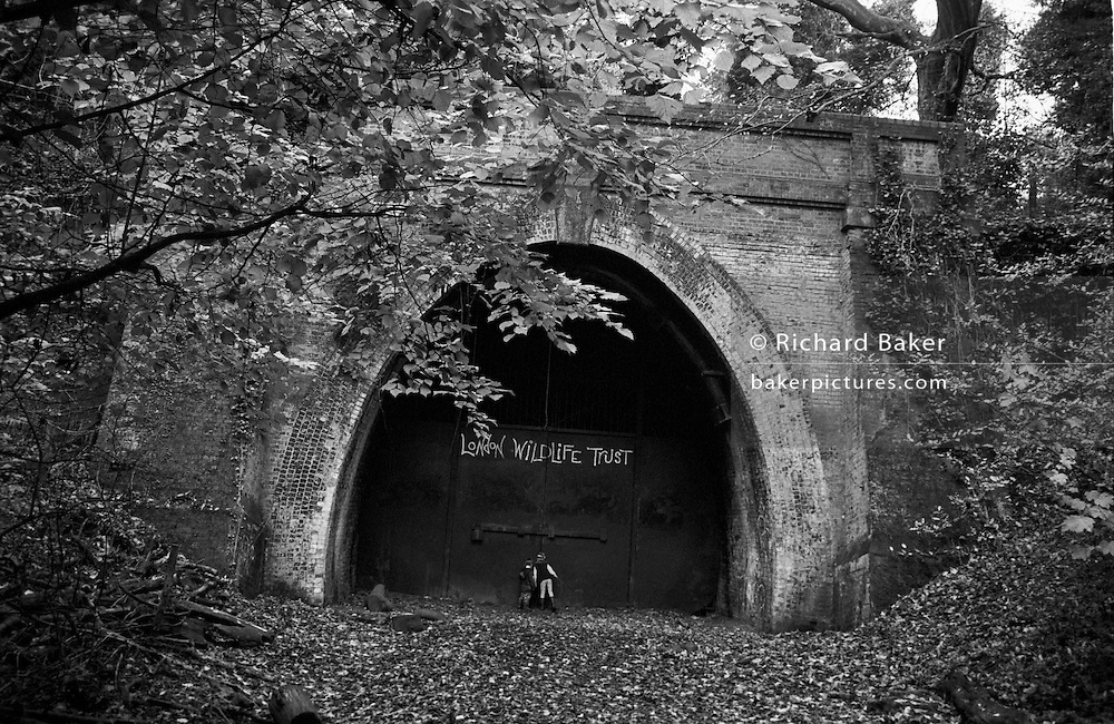 "Peering through a hole in the huge metal door of an old Victorian tunnel, two children stand on the place where a railway once emerged from this brick entrance - a link between nearby Dulwich and the Crystal Palace. Now the London Wildlife Trust maintains this once-wild wood at Sydenham, South London, England, which has reverted to forest again, 40 years after (one of the first the electrified railways) line fell silent. The brother and sister look through to see if there is light at the end of this tunnel but it has long been bricked up, sealed to deter vandals and danger to all. It is Autumn and the leaves on the beech and oak trees are about to fall, adding to the already organic deep forest floor. From a personal documentary project entitled ""Next of Kin"" about the photographer's two children's early years spent in parallel universes. Model released"