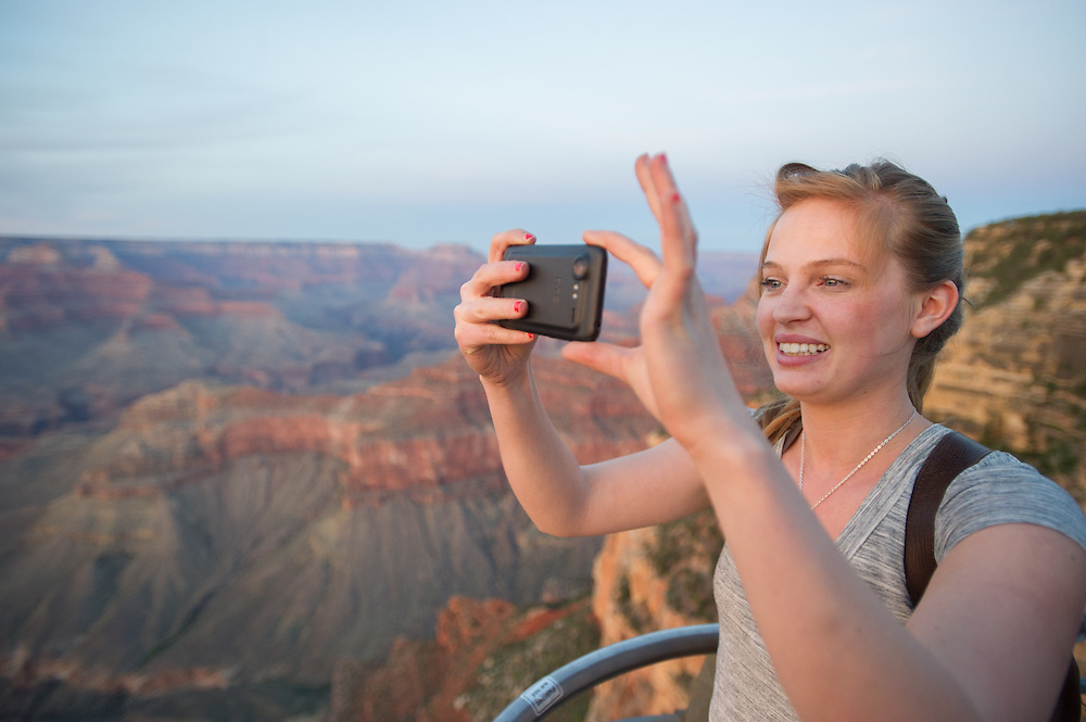 Young Woman Taking Cellphone Picture of Grand Canyon