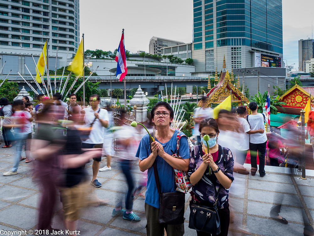 29 MAY 2018 - BANGKOK, THAILAND: People pray at the entrance to Wat Hua Lamphong while others walk in a procession during Vesak observances at Wat Hua Lamphong in Bangkok. Vesak is the Buddha's birthday, and one of the most important holy days in the Theravada Buddhist religion. Many Thais visit their local temples for Vesak and rededicate themselves to the Dharma, listen to talks about Buddhism and make merit by bringing flowers to the temple.     PHOTO BY JACK KURTZ