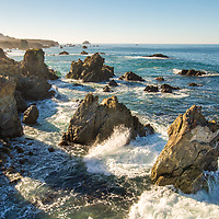 Morning sun peering over the hills as the waves break on the rocks in Big Sur, CA. © John McBrayer2015