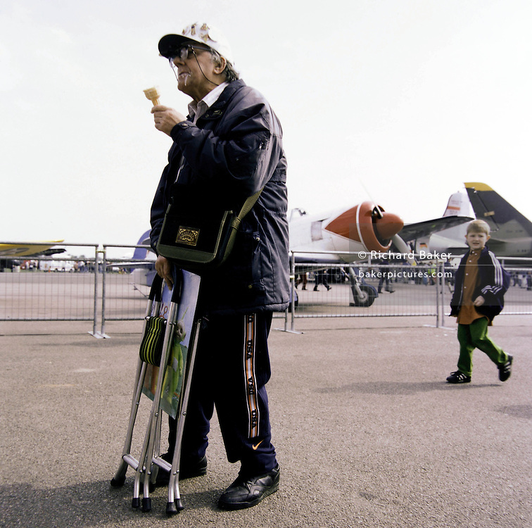 An aviation enthusiast eats an ice cream during an airshow at North Weald in Essex, southern England. Slurping on the melting ice cream, the odd-looking man wearing an anorak looks to unseen aircraft parked alongside the public areas during the hours before the flying displays commence at this small airfield north of London.