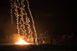 "© Licensed to London News Pictures . 23/10/2016 . Calais , France . Riot police use tear gas to disperse camp dwellers at the Calais migrant camp known as "" The Jungle "" , in Northern France , on the evening before the start of the eviction and destruction of the camp . Photo credit: Joel Goodman/LNP"