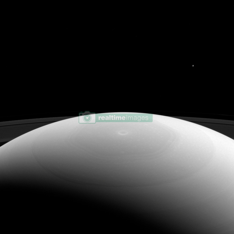 March 27, 2017 - Space - From high above Saturn's northern hemisphere, NASA's Cassini spacecraft gazes over the planet's north pole, with its intriguing hexagon and bullseye-like central vortex. Saturn's moon Mimas is visible as a mere speck near upper right. At 246 miles (396 kilometers across) across, Mimas is considered a medium-sized moon. It is large enough for its own gravity to have made it round, but isn't one of the really large moons in our solar system, like Titan. Even enormous Titan is tiny beside the mighty gas giant Saturn. This view looks toward Saturn from the sunlit side of the rings, from about 27 degrees above the ring plane. The image was taken in green light with the Cassini spacecraft wide-angle camera. (Credit Image: ? JPL-Caltech/NASA via ZUMA Wire/ZUMAPRESS.com)