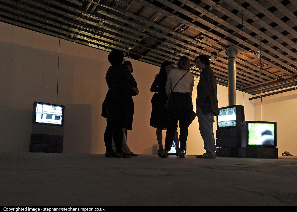 © licensed to London News Pictures. LONDON, UK.  22/06/11. Artist Tom Pope talks to visitors in his installation featuring TV's and video. Students present their work at The Royal College of Art's Fine Art Graduate Show 2011. The show runs from 24th June-3rd July 2011. Mandatory Credit Stephen Simpson/LNP