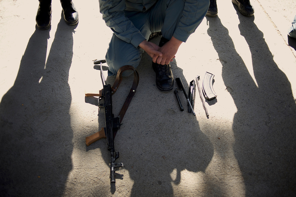A Afghan National Police (ANP) cadet kneels behind a dismantled AK-47 during weapon handling training in the yard of the Afghan Nacional Police Academy in Kabul.