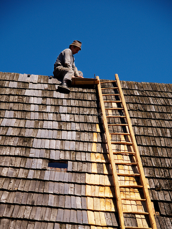 A man repairing a roof in Vikolinec a traditional wooden village in Eastern Slovakia.