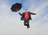 Business man flying with umbrella mid-air outdoors