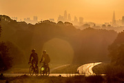 UNITED KINGDOM, Richmond Park: 14 May 2019 <br /> Early morning cyclists make their way through Richmond Park in front of the London skyline this morning as the sun rises on another fine day of weather across The UK. Temperatures are set to reach 19C in the capital and potentially higher in the Midlands.