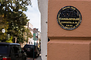 Carolopolis Pro Merito Award medallion on a historic home in Charleston, SC.