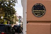 Carolopolis Pro Merito Award medallion on a historic home in Charleston, SC.