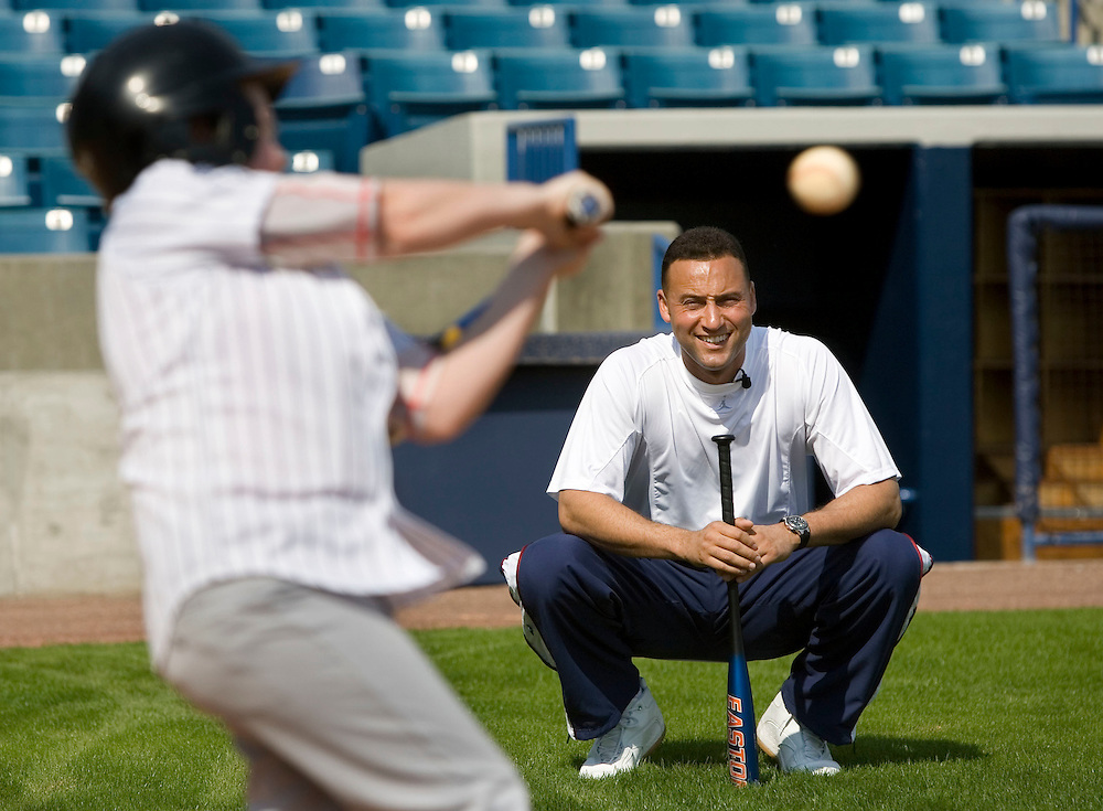"""New York Yankee's Derek Jeter, right, smiles while watching Gavin Leaonard, 9, of Bristol, Virginia take batting practice during the Upper Deck, """"Play Ball! with Derek Jeter"""" clinic on Saturday, February 10, 2007 at Legends Field in Tampa, Florida.  Justin Topa, 15, of Binghampton, New York, Jordan Boone, 10, of Las Vegas, Nevada, Bryce Porter, 10, of Costa Mesa, California and Gavin Leonard, 9, of Bristol, Virginia, each won the grand prize to meet Jeter through various promotions on www.UpperDeckKids.com in 2006. UPPER DECK/Scott Audette"""