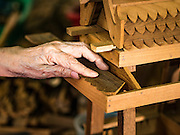 02 NOVEMBER 2016 - BANGKOK, THAILAND:  HONG, 77 years old, the matriarch of the last family making spirit houses in the Ban Fuen community, checks the fit of a roof overhang on a spirit house being made in her home workshop. There used to be 10 families making traditional spirit houses out of teak wood in Ban Fuen, a community near Wat Suttharam in the Khlong San district of Bangkok. The area has been gentrified and many of the spirit house makers have moved out, their traditional wooden Thai houses replaced by modern apartments. Now there is just one family making the elaborate spirit houses. The spirit houses are made by hand. It takes three days to make a small one and up to three weeks to make a large one. Prices start at about $90 (US) for a small one. The largest, most elaborate ones can cost over $1,000 (US). Almost every home and most commercial buildings in Thailand have a spirit house, which is a shrine to the protective spirit of a the land. Spirit houses are also common in Burma, Cambodia, and Laos.       PHOTO BY JACK KURTZ