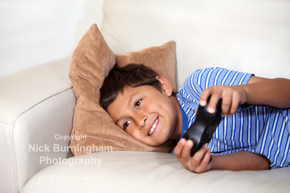 Young boy playing computer game while relxing on the sofa