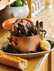 Cooked mussels in copper pot on side board