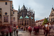 Tourist groups and visitors passing the St. George's Square (Namesti U Svateho Jiri) at Prague Castle. In the back St. Vitus Cathedral. This cathedral is a prominent example of Gothic architecture and is the largest and most important church in the country.