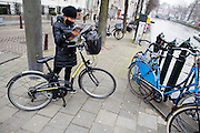In Amsterdam zoekt een vrouw met een huurfiets de weg op een plattegrond.<br /> <br /> In Amsterdam a woman with a rental bike is looking for the way on a map.