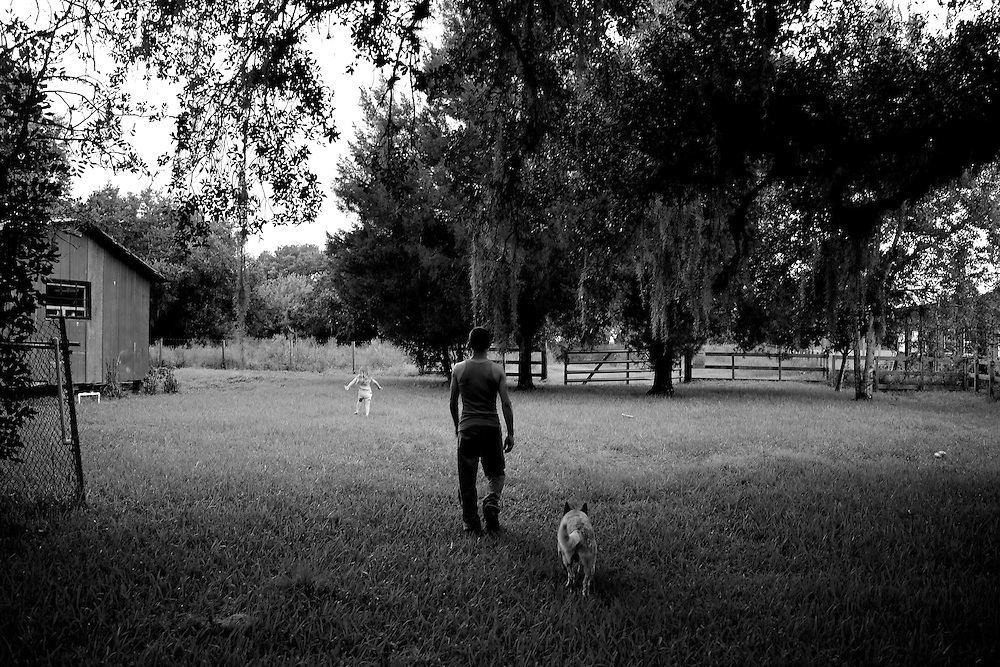 "Don Norton walks with his dog and one of his daughters, Trinity, through their back yard in Alva, Fla. Norton, a single father with custody of his two daughters, lost a third daughter after she locked herself in his car on a summer day and suffocated in the heat. ""I can't speak for other people: what they go through; how they handle it. 'Cause it was crazy. And I did go through the whole...I got into drugs. I got into drinking. I got into this and I went through the whole crazy phase,"" Norton said."