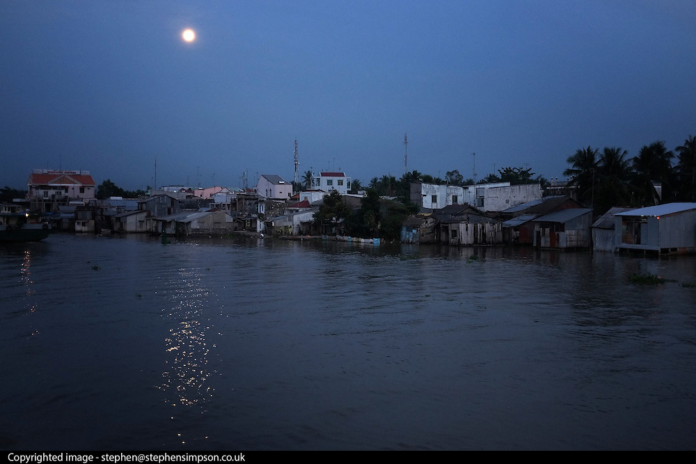 © Licensed to London News Pictures. 08/01/2012. A village lit by moonlight alongside the Bassac River in the Meekong Delta, Vietnam. Photo credit : Stephen Simpson/LNP