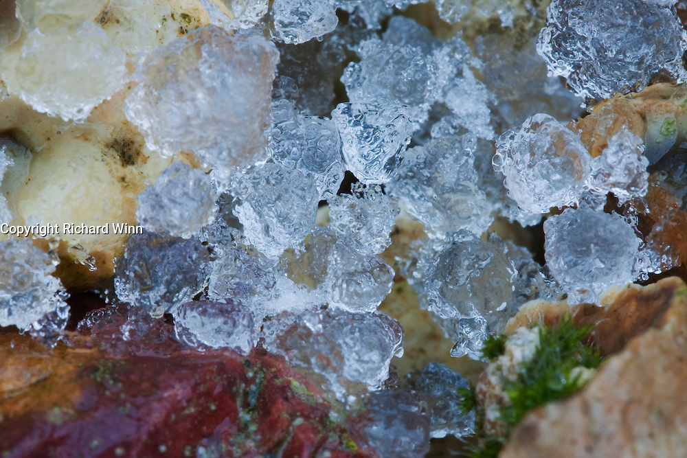 Macro of some hailstones approximately 1-2 mm diameter after they had started melting and lost their opacity to show some of the colours from the pebbles underneath.