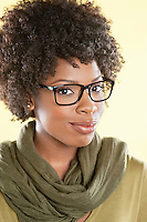 Portrait of an African American woman wearing glasses with a stole round her neck over colored background