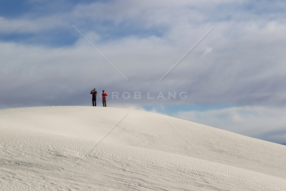 two people back to back photographing in White Sands, NM
