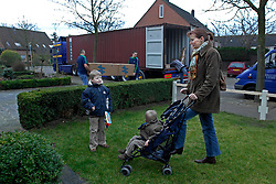 OUD-HEUSDEN, THE NETHERLANDS - FEB-23-2007 - Ingrid Diepeveen keeps a watchful eye on her sons Max, 6, and Niek, 2, as movers from De Haan Removals fill a shipping container with the their household belongings which will be shipped to Japan. The Diepeveen are moving from their home in the Netherlands to Kobe, Japan where Mr. Diepeveen will work for the Dutch multi-national company Wartsila Propulsion B.V.  (PHOTO / JOCK FISTICK)