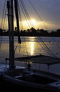 Sunset over the River Nile, Egypt, anchored felucca in foreground.