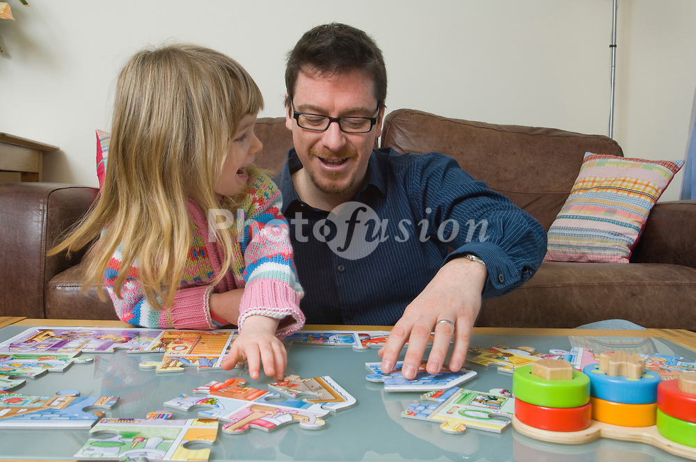 Father & 4 year old daughter doing jigsaw together UK