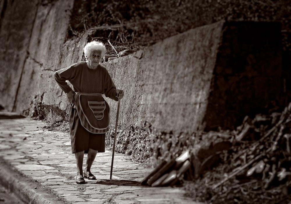Greek grandma walking with a cane - B&W