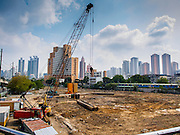"""03 APRIL 2014 - BANGKOK, THAILAND:  A construction site for urban infill at the corner of Rama IV and Ratchadaphisek Streets at the entrance to Khlong Toey Market. Khlong Toey (also called Khlong Toei) Market is one of the largest """"wet markets"""" in Thailand. The market is located in the midst of one of Bangkok's largest slum areas and close to the city's original deep water port. Thousands of people live in the neighboring slum area. Thousands more shop in the sprawling market for fresh fruits and vegetables as well meat, fish and poultry.     PHOTO BY JACK KURTZ"""