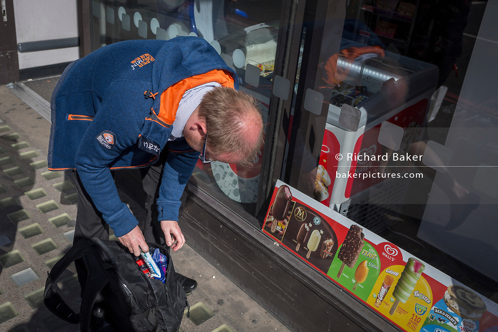 A man bends down to place a Bounty bar into his holdall bag, on 14th September 2017, in London, England.